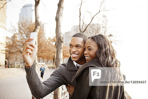 Cheerful couple clicking selfie with smart phone on sunny day