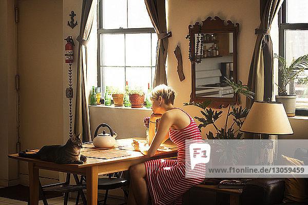 Seitenansicht einer Frau  die zu Hause am Tisch sitzt
