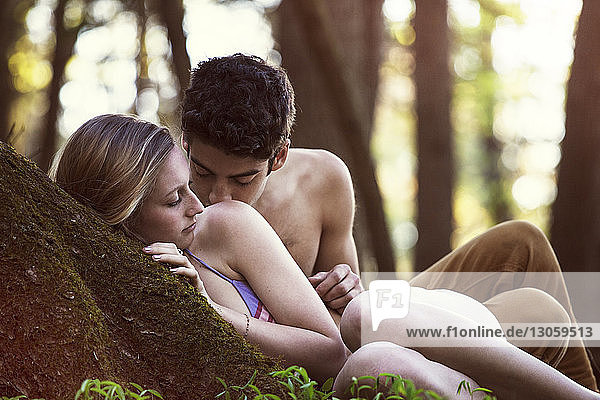 Couple romancing by tree in forest