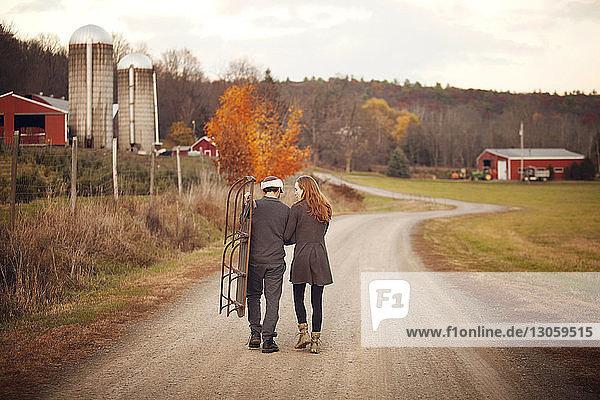Rückansicht eines Ehepaars mit Schlitten  das auf Straße und Feld läuft