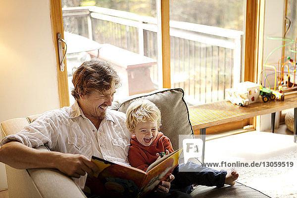 Vater liest mit dem Sohn ein Buch  während er zu Hause auf dem Sofa sitzt