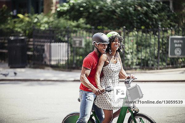 Fröhliches Paar mit Fahrrad auf der Straße in der Stadt stehend