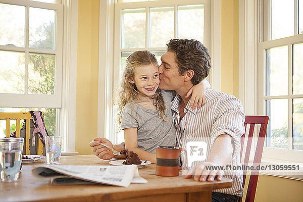 Vater küsst Tochter  während er auf einem Stuhl am Tisch sitzt