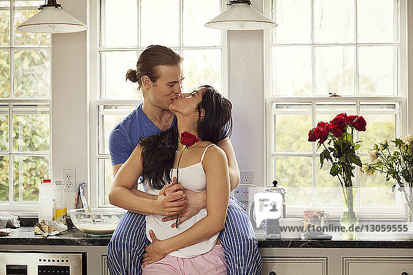 Passionate couple kissing while standing by kitchen counter at home