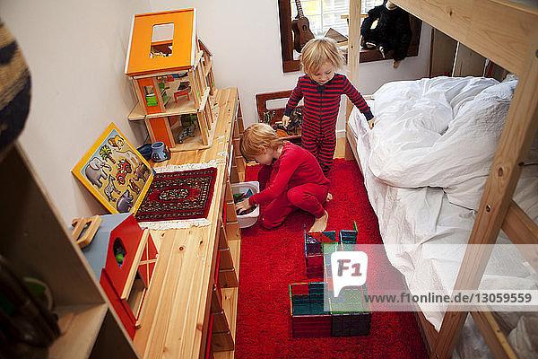 Kinder ordnen Spielzeug im Schlafzimmer an