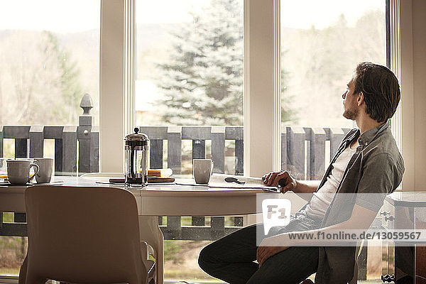 Man looking away while sitting on chair by table at home