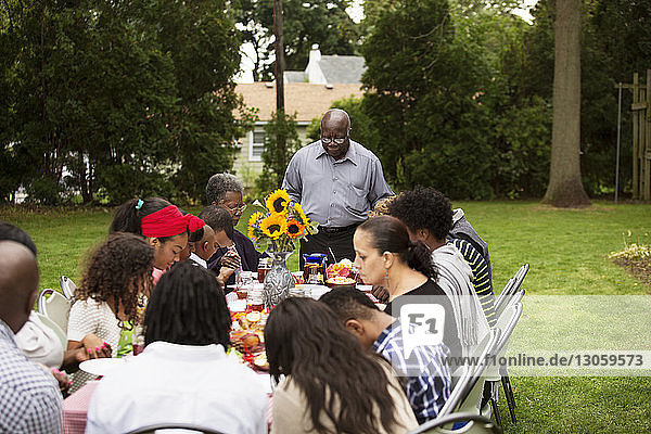 Family and friends having food at table in backyard