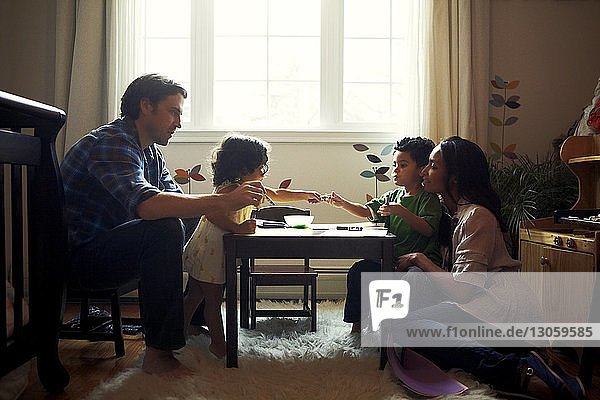 Parents looking at children drawing at table in home