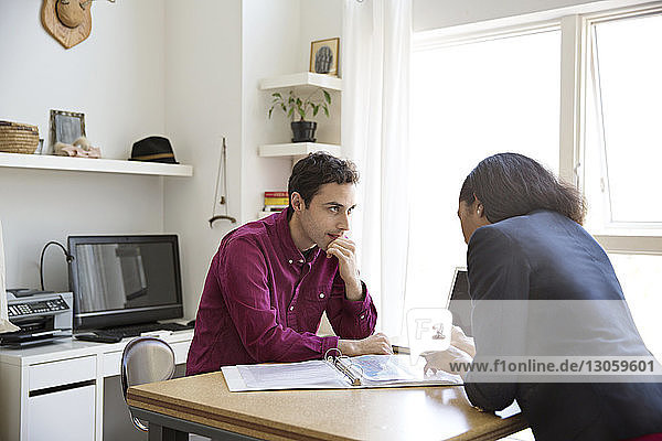 Business people having discussion over documents at desk in creative office