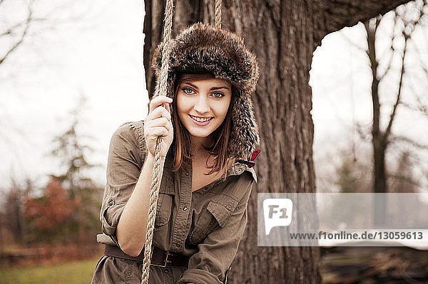 Porträt einer schönen Frau mit Pelzmütze  die ein Seil hält