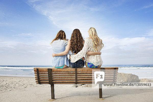 Rückansicht von Freunden  die am Strand auf einer Bank sitzen