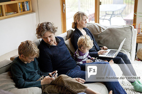 Family using laptop and mobile phone while sitting on sofa at home