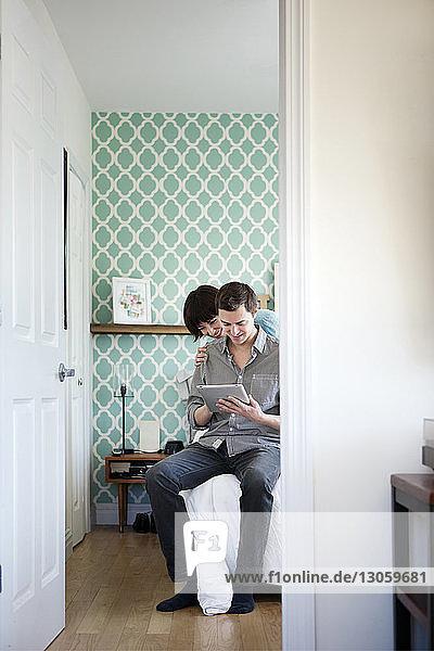 Glückliches Paar betrachtet Tablet-Computer  während es zu Hause im Bett sitzt