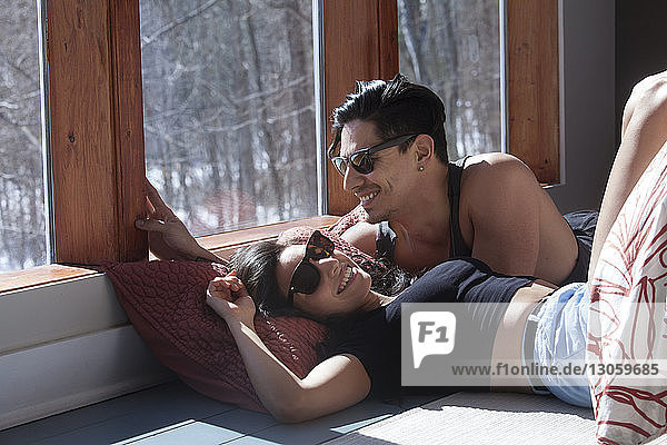 Happy couple lying on floor by window at home