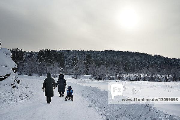 Rückansicht der Familie auf schneebedecktem Feld gegen den Himmel