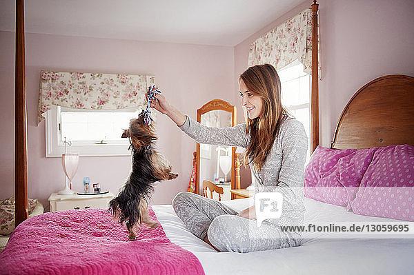 Glückliche Frau spielt mit Hund im Schlafzimmer