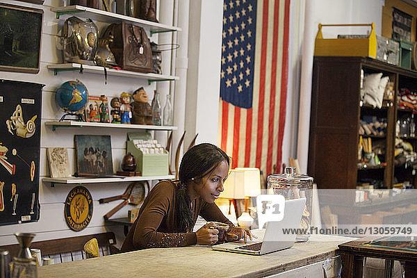 Frau trinkt Kaffee  während sie im Café einen Laptop benutzt