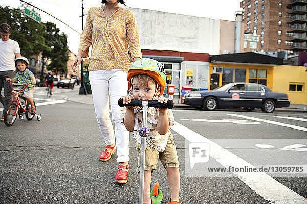 Portrait of boy riding push scooter with family on streets in city