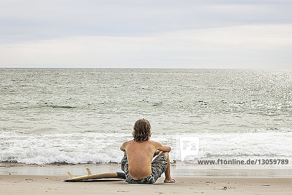 Rear view of man with surfboard sitting at shore