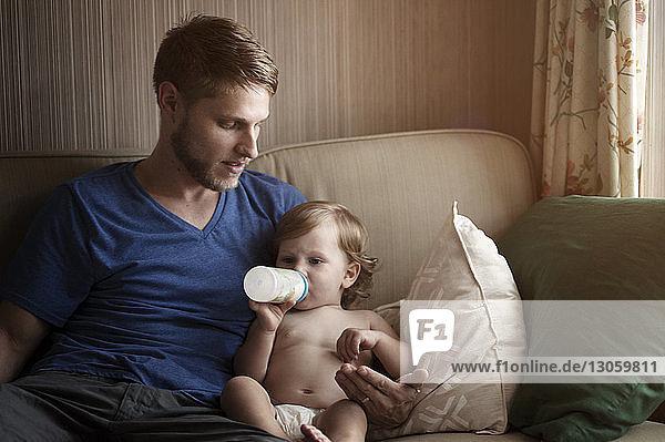 Vater sieht Sohn beim Milchtrinken an  während er sich auf dem Sofa entspannt