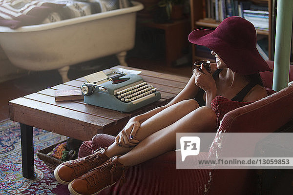 Happy woman drinking coffee while sitting by typewriter at home