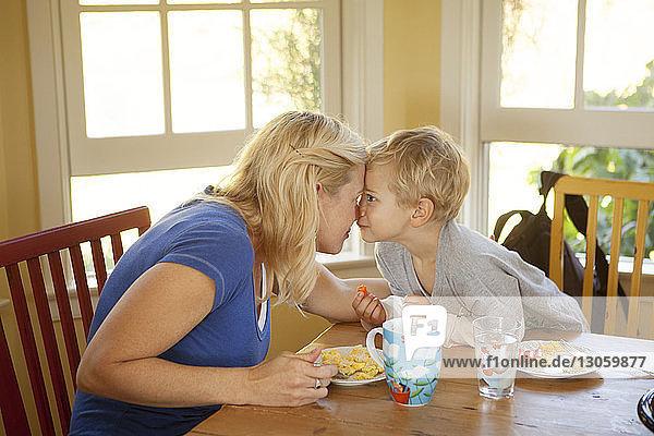 Verspielte Mutter und Sohn sitzen auf Stuhl am Tisch