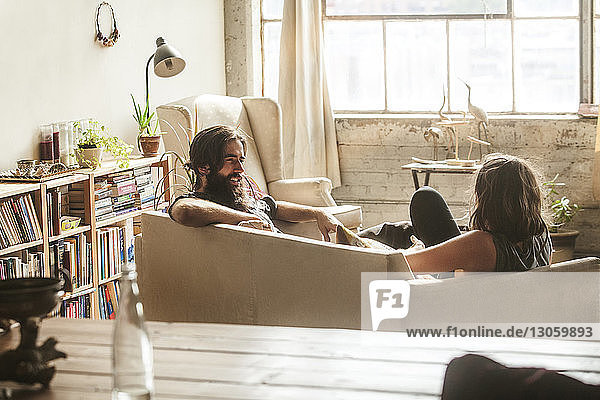 Couple talking while sitting in living room at home