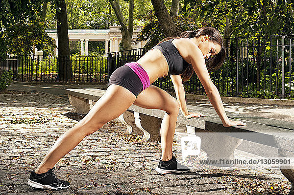 Side view of sporty woman exercising at park
