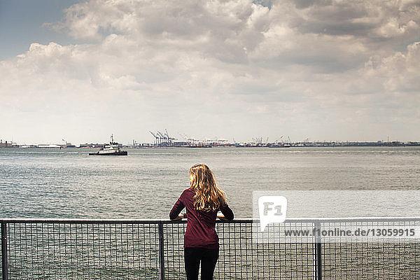 Rückansicht einer Frau  die an der Reling gegen den Fluss steht