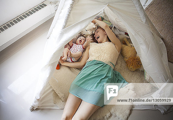 High angle view of mother playing with daughter while lying in tent at home