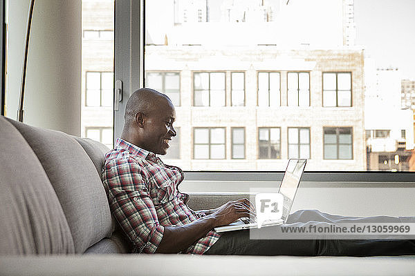 Side view of happy man using laptop computer while sitting on sofa at home