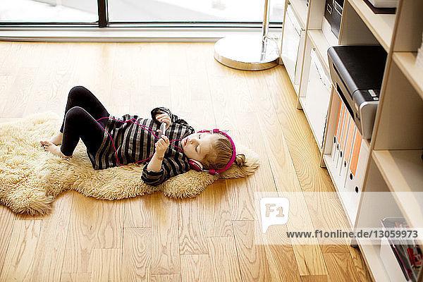 Hochwinkelaufnahme eines Mädchens  das Musik hört  während es sich zu Hause auf dem Teppich entspannt