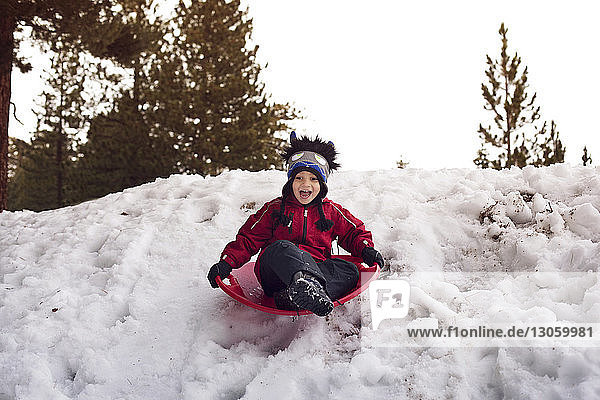Boy screaming while tobogganing on sled at snowfield