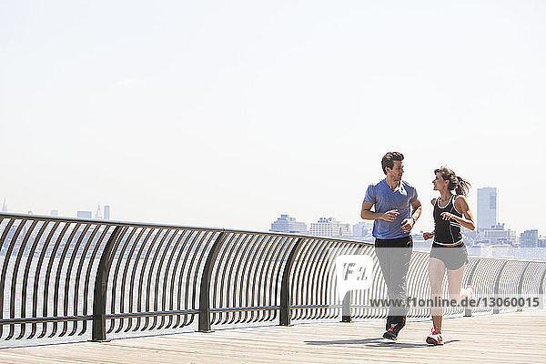 Paar Jogging durch Geländer gegen den Himmel