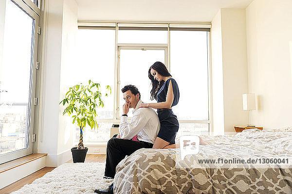 Seitenansicht eines Paares  das sich auf dem Bett in einem hell erleuchteten Schlafzimmer entspannt