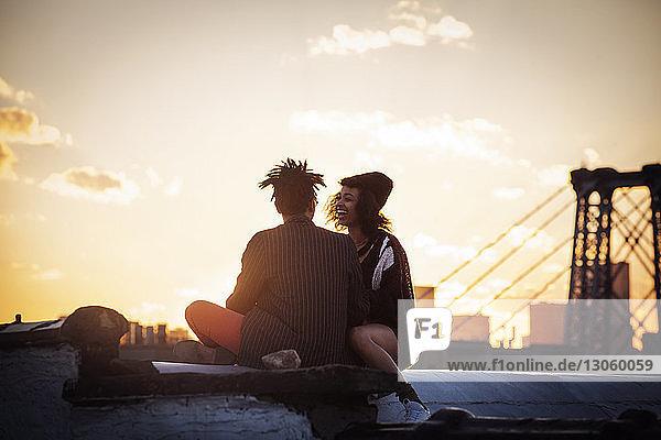Fröhliches Paar sitzt bei Sonnenuntergang auf Stützmauer