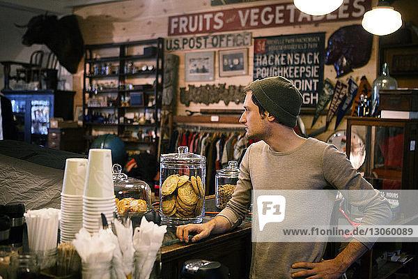 Mann schaut weg  während er am Tresen im Cafe steht