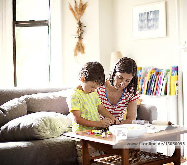 Mutter betrachtet Sohn beim Spielen mit Spielzeug am Tisch im Wohnzimmer