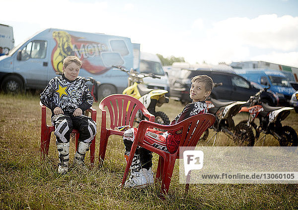Happy boys sitting on chairs at grassy field