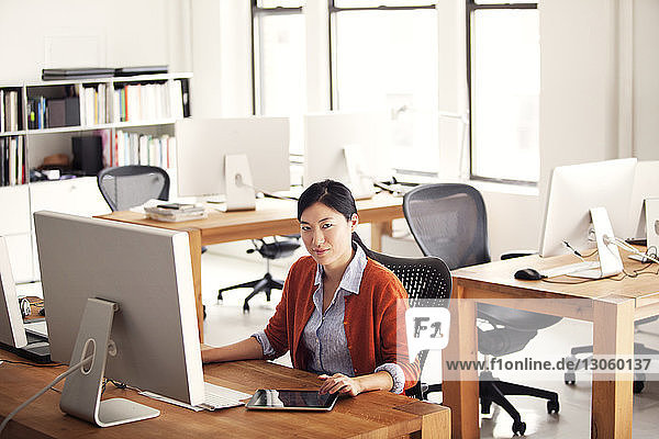 Portrait of woman using computer while sitting at office