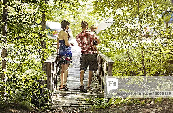 Rückansicht eines Mannes  der einen Sohn trägt  während er mit einer Frau auf einem Steg im Wald spazieren geht