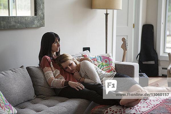 Mutter und Tochter entspannen sich zu Hause auf dem Sofa
