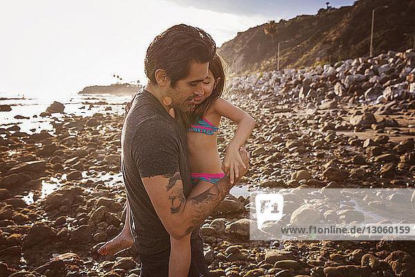 Vater trägt Tochter bei Sonnenuntergang am Strand