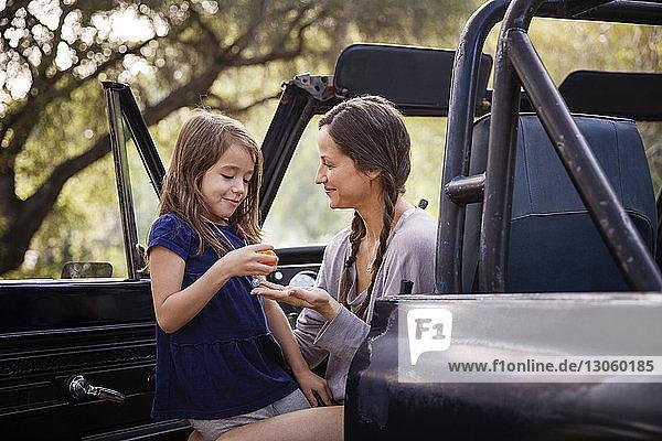 Mädchen schenkt der im Pickup sitzenden Mutter eine Orange