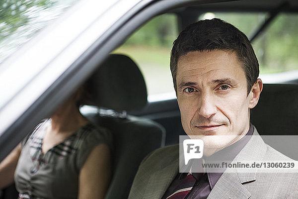 Porträt eines Mannes  der mit einer Frau im Auto sitzt