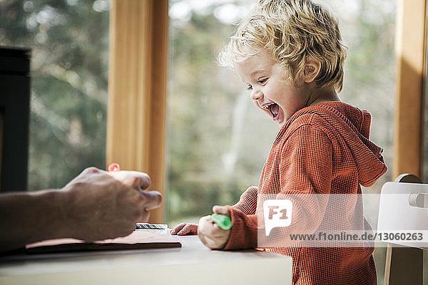 Fröhlicher Junge lernt schreiben  während er zu Hause beim Vater sitzt