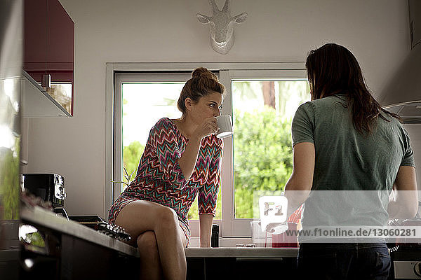 Woman with coffee cup looking at man while sitting on kitchen counter