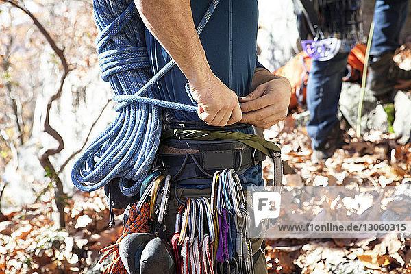 Mitschnitt eines Mannes mit Freund bei der Vorbereitung zum Klettern