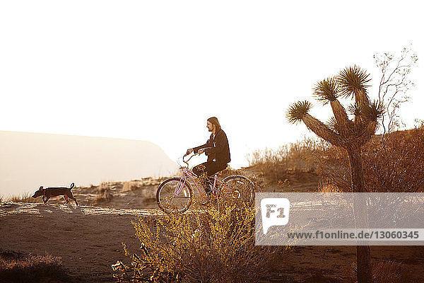 Seitenansicht eines Mannes beim Fahrradfahren auf dem Feld bei klarem Himmel