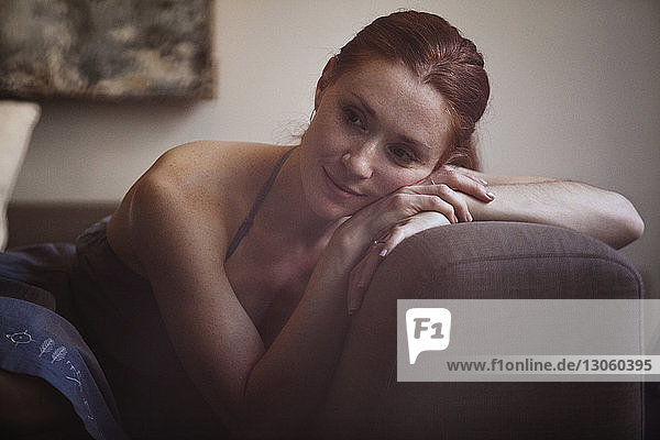 Thoughtful woman leaning on sofa at home